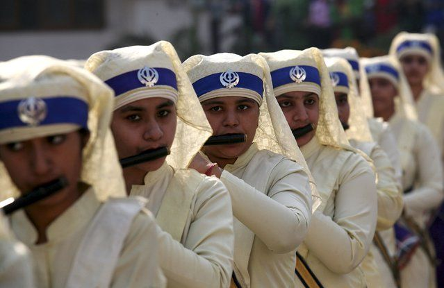 Sikh girls play flutes as they take part in a religious procession on the eve of the 546th birth anniversary of Guru Nanak Dev, the first Sikh Guru and founder of Sikh faith, in Amritsar, India, November 24, 2015. (Photo by Munish Sharma/Reuters)