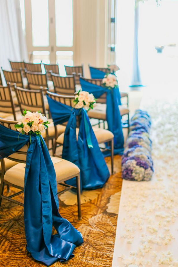 Elegant aisle markers: Blue satin sashes with pink rose bouquets (Photo by Clane Gessel Photography)