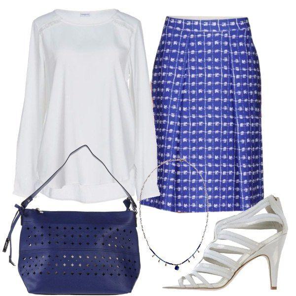 Alla gonna blu con piccoli disegni bianchi abbiniamo la blusa con particolari in pizzo, i sandali a listino col tacco a cono, la borsa blu con impunture e la delicata collana con pietre.