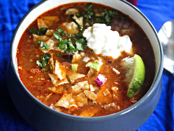 Rich chicken tortilla soup, made from slow-simmered chicken thighs, joins quintessential toppings—avocado, red onion, sour cream, cilantro, cheese, tortillas, limes and hot sauce—in this simple, sustaining slow-cooker meal. The broth gets both depth and brightness from chili powder, smoky chipotles, fire-roasted tomatoes, cumin, and a couple of secret ingredients: unsweetened cocoa powder and apple cider vinegar.