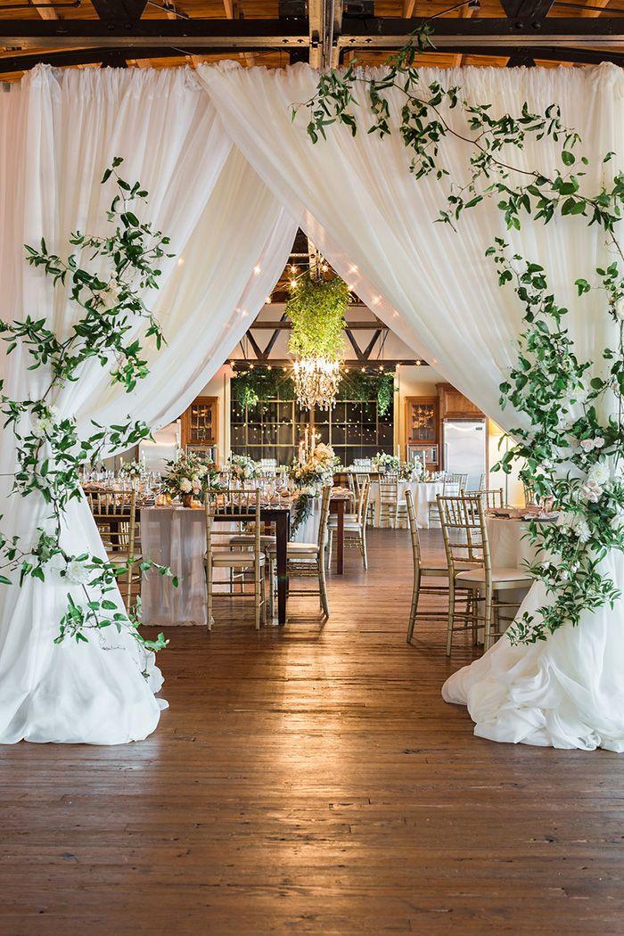 Barn Wedding Reception with a Draped Entrance with Modern Greenery https://heyweddinglady.com/earthy-organic-wedding-style-modern-greenery/ #weddings #wedding #weddingideas #realweddings #southernweddings #weddingreception #reception #greenery #weddingdecor #weddingflowers