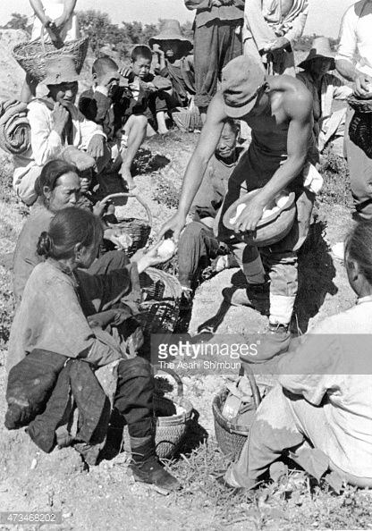 Japanese Imperial Army soldiers distribute rice balls to Chinese refugees as the result of the Yellow River Flood which created by the Chiang KaiShek...