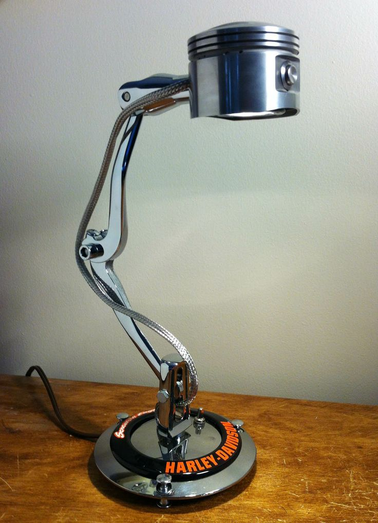 What we have here is an HD piston halogen light connected on two shifter arms wrapped by a stainless steel line. It stands on a Harley-Davidson derby cover with a screaming eagle emblem. A push switch fires it up.