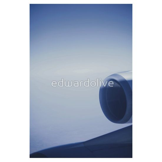 Jumbo jet airplane wing engine in flight flying over blue sky photo. Jumbo jet aeroplane wing engine in flight flying over blue sky. Color digital artistic photograph by Edward Olive portrait photographer from Madrid Spain.