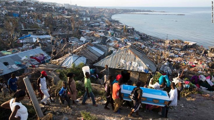Residents try to move the remains of a pregnant woman killed by Hurricane Matthew in Jeremie, Haiti.