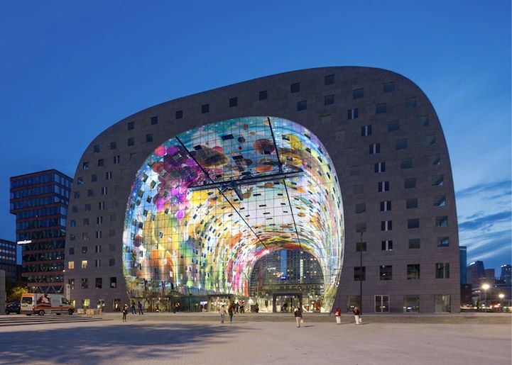 The Markthal Rotterdam, a covered food market and housing development in the Netherlands, was designed by Dutch architects MVRDV. The most striking feature of this arched structure is its colorful mural titled Cornucopia by artists Arno Coenen and Iris Roskam. It wraps around the interior ceiling and occupies over 36,000 square feet of space. Broken up into squares, each part of the image was printed onto perforated aluminium panels that were then attached to acoustic panels for noise…