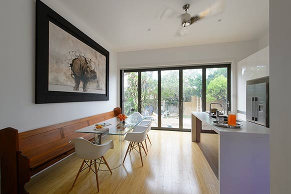 Striking painting of rhino breaking through the wall. Love the church pew seat mixed with the modern glass table and white chairs. The Block All Stars: Mark and Duncan's House