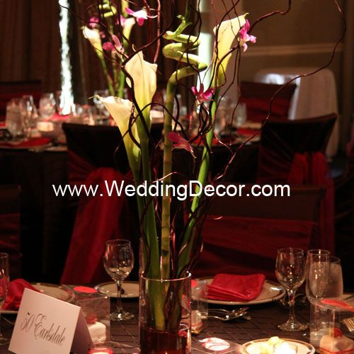 Wedding Centerpiece - calla lilies, curly willow, curly bamboo and fuchsia dendrobium orchids in a small cylinder vase
