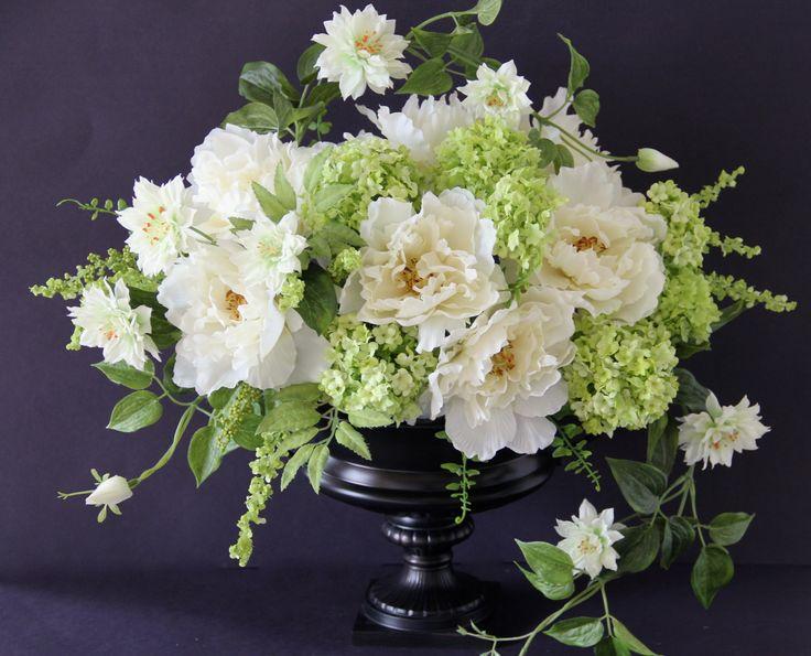 Silk flowers arrangement.White peonies ,viburnum,clematis vine in black metal urn.Design by Simone Vartan.