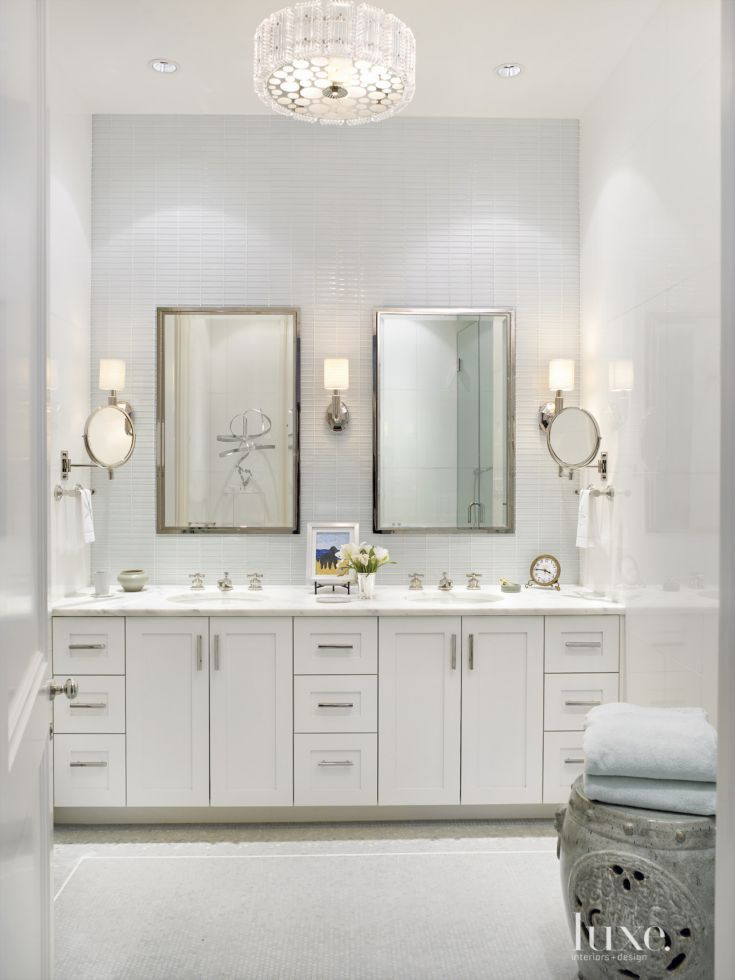High-gloss paint and glass wall tiles help to bounce bright light throughout the windowless master bathroom, where the designers added subtle touches of the owner's personality to the clean and crisp sanctuary. A stainless-steel sculpture on a clear Lucite stand can be seen in the mirror's reflection.