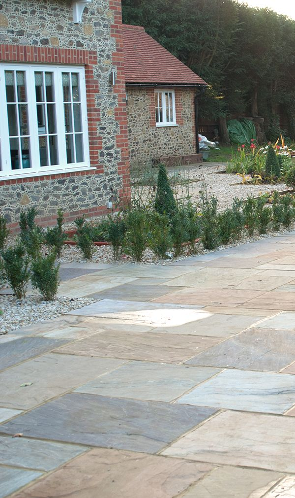 Paving stones create a practical yet attractive outdoor space. Shown here: Saxon Swirl sandstone paving stones.