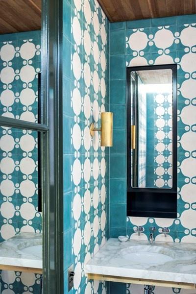 De gastenbadkamer contrasteert fel met de andere badkamer en roept een mediterraanse sfeer op. De eigenaars wilden met deze kamer bovenal een verrassende stijl neerzetten.