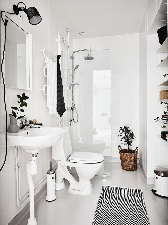 Small Swedish Bathroom With A Black Sconce, And Woven Storage Bins