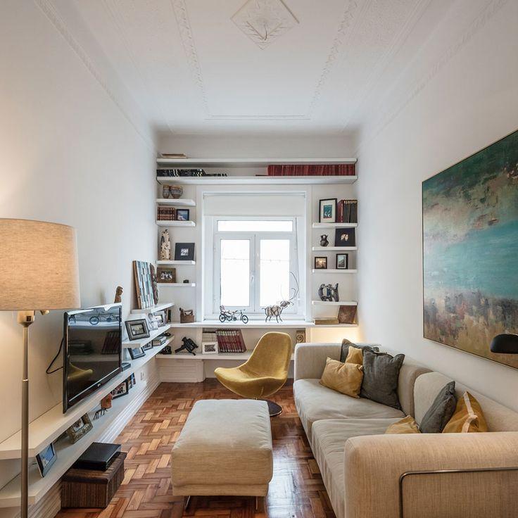 Decoração de sala de estar de apartamento pequeno, decoração minimal, marcenaria, luz natural, sofá bege, cadeira amarela, abajur, obra de arte.