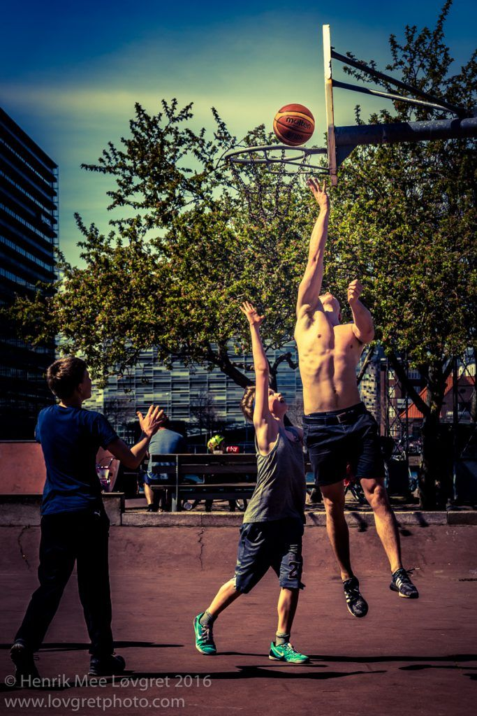 Boys enjoying the moment in the sun playing a game of street basket