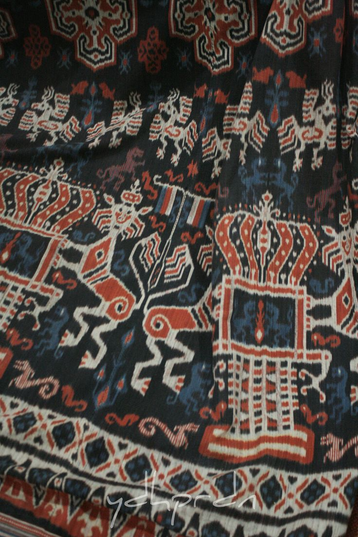 """Hinggi or men's wrap from Sumba in """"mahang"""" pattern, a depiction of a climbing lion protecting the crown which clearly inspired by Dutch coat of arms. The use of Dutch traditional design on sumba textile signaling that the textile was meant to be worn by a highest class of nobleman or """"maramba"""". Done in very neat and dense weaving with 4 color including red, blue and black made out of natural dyes. Original pattern was derived from Rende, but this textile made in Mauliru - Sumba."""