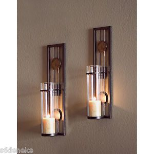 Wall Sconces For Candles    Sconces have cylindrical candle holders made of clear glass. Light your pillar candles in these wall scones without fear of the hot wax spilling or someone knocking the candle over.