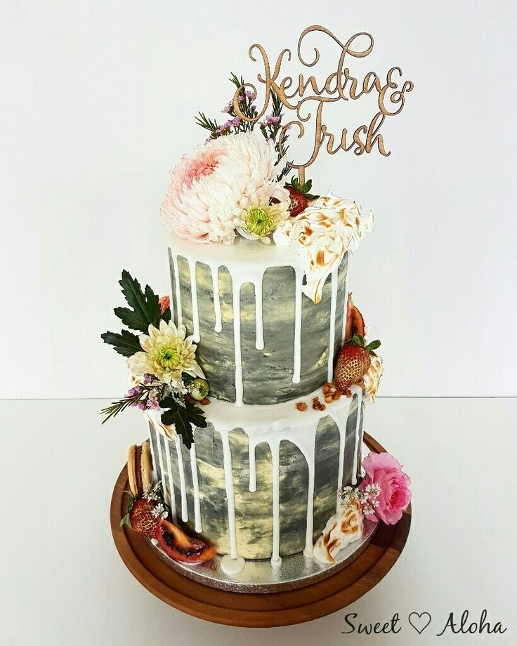 Pretty and industrial drip cake with fresh flowers and meringue