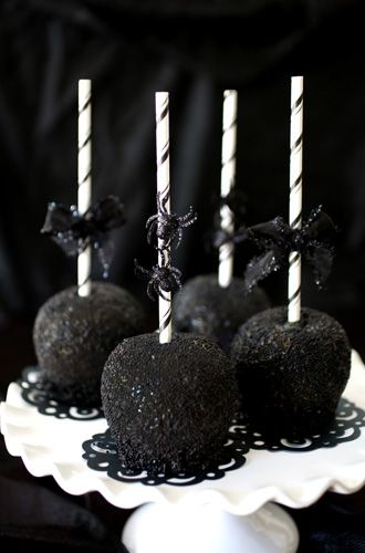 Black-as-Night Caramel Apples Caramel apples Decorative lollipop sticks Black sanding sugar Black jimmies Black plastic spiders (for decoration) Black ribbon (for decoration) Glue dots Directions  1 Fill a bowl with the jimmies and sugar.  2 Once the apples have set but are still tacky, roll apples in the jimmies and sugar to coat completely.  3 Adhere a spider or ribbon to straw with a glue dot.