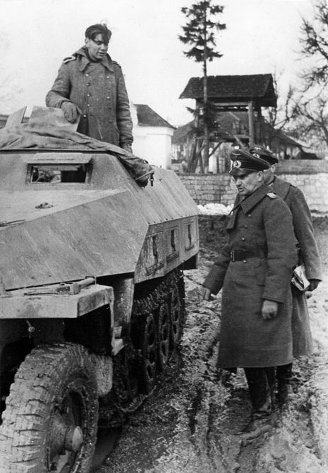 "Field Marshal Walter Model inspecting a young soldier serving in an Sd.Kfz.251 AusfD in April 1944. On 31 January 1944 Model was named Commander-in-Chief of Army Group North. He was the first commander in the Panzer-Divisions to introduce the ""Shield and Sword"" policy which stated that retreats are tolerable, but only if they paved the way for a counterstroke later."