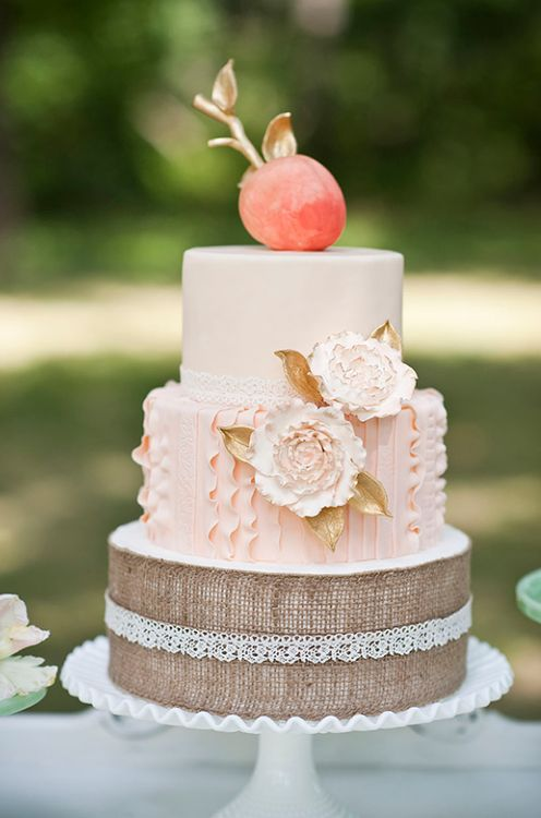 beautiful pink wedding cake with the base tier wrapped in burlap with lace