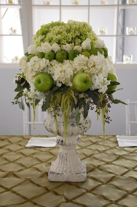Using a Biedermeier style, this arrangement has a center utilizing all green hydrangea, then a layer of pure white roses, accented by a circular pattern of limes, then a layer of all white hydrangea finished off with a layer of alternating green apples and white stock clusters while seeded eucalyptus and hanging green amaranthus added just enough disorganization to this structured arrangement.
