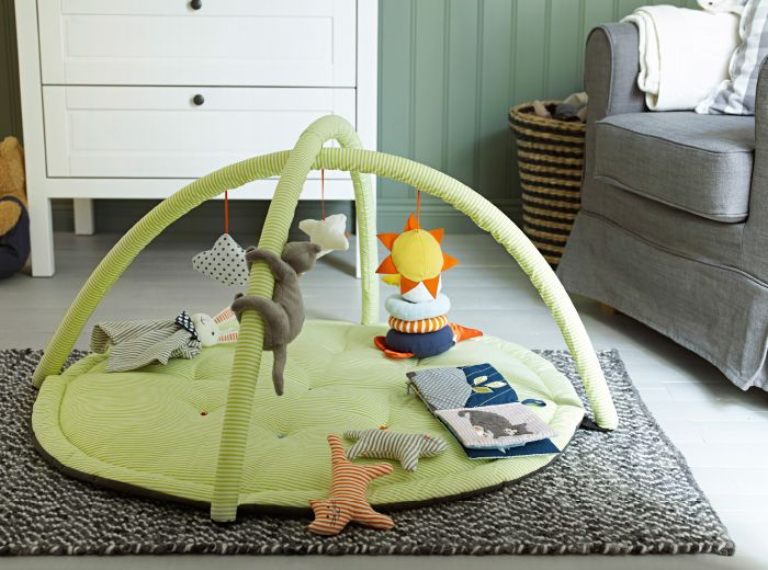 A Children's IKEA baby gym with soft toys on a rug in the nursery.