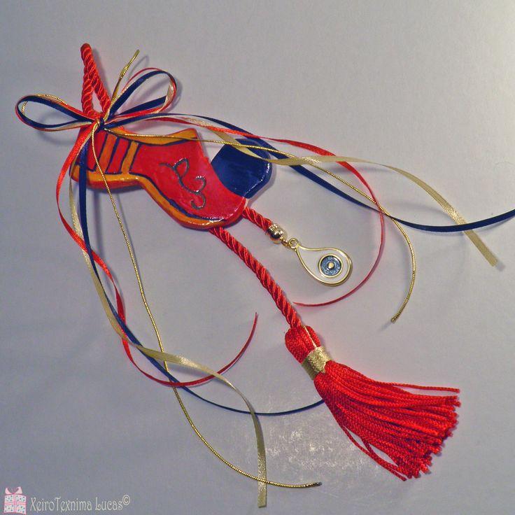Ελληνικό, χειροποίητο, κόκκινο, κεραμικό τσαρούχι, δεμένο με σατέν κορδέλες σε αντίστοιχα χρώματα, πάνω σε μία εντυπωσιακή κόκκινη φούντα. Στην άκρη του γουριού, κρέμεται ένα μεταλλικό μάτι με λευκό και γαλάζιο σμάλτο. Περισσότερα γούρια και υλικά για γούρια θα βρείτε στο www.lucas.com.gr . Greek handmade traditional ceramic rustic folklore shoe tsarouhi, decorated with ribbons and a metal evil eye with white and light blue enamel.
