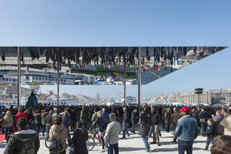 A polished steel canopy reflects visitors walking underneath at this events pavilion in Marseille's harbour by UK firm Foster + Partners