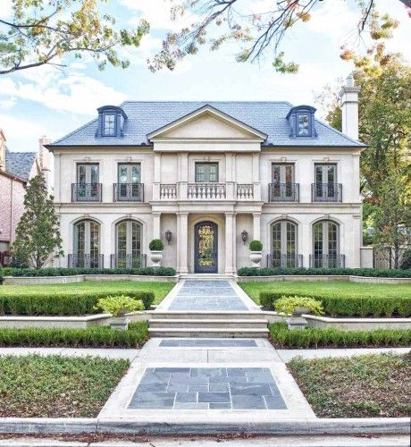"""Lovely French style home with quasi """"mansard"""" roof, ironwork around windows,  lovely balcony, dormers on third floor and great looking long stone wide walkway leading up to the door."""