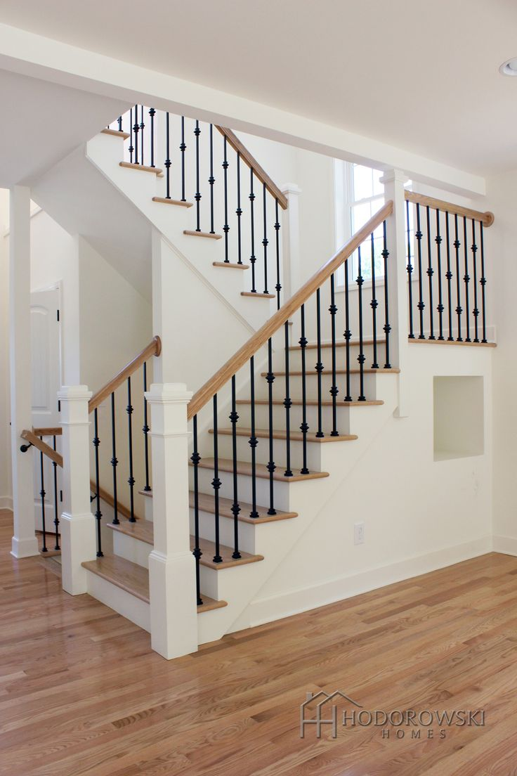 """Natural oak hardwood floor with matching """"Natural"""" oak treads paired with alternating double and single box wrought iron spindles and large white newel posts."""