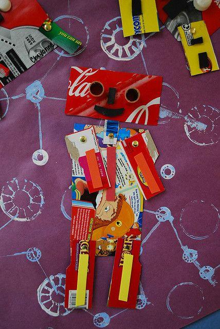 Achtergrond stempelen... met K'nex? Vervolgens een robot knippen en plakken van stukken restkarton.
