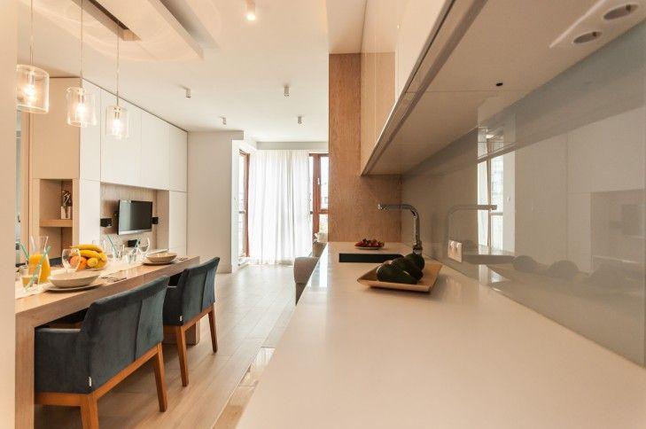 Aranżacja wnętrza kuchni otwartej na salon. Jasna, błyszcząca zabudowa została połączona z drewnianymi podłogami i błękitnymi dodatkami.