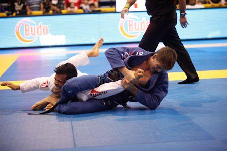 Clé de bras en jujitsu Bresilien. On peut voir à la douleur qui se dessine sur le visage de la victime que le mouvement est correctement réalisé.