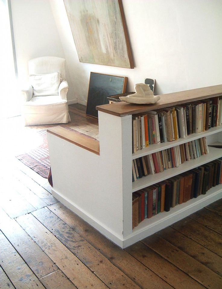 short bookshelf as room divider with a built-in trunk-style storage bench.