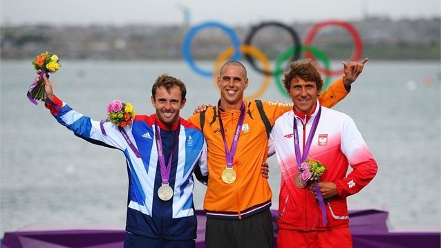 Gold medallist Dorian Van Rijsselberge (C) of Netherlands celebrates with silver medallist Nick Dempsey (L) of Great Britain and bronze medallist Przemyslaw Miarczynski (R) of Poland following the Men's RS:X Sailing on Day 11 of the London 2012 Olympic Games at the Weymouth & Portland venue
