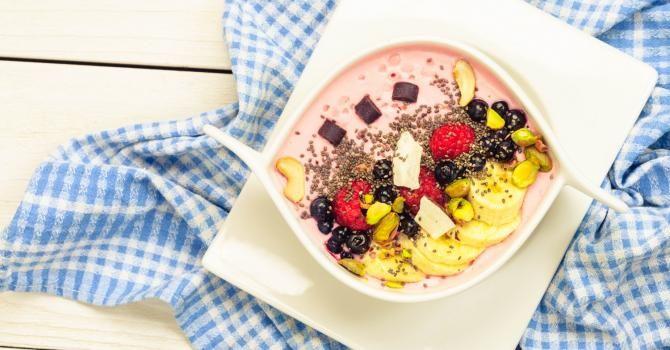 Smoothie bowl déstructuré aux fraises, pistaches, banane, myrtilles, framboises, noix de cajou, graines de pavot et chocolat