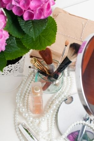 Beauty and make up concept table mirror flowers perfume jewelry and makeup brushes on a white table  Stock Photo