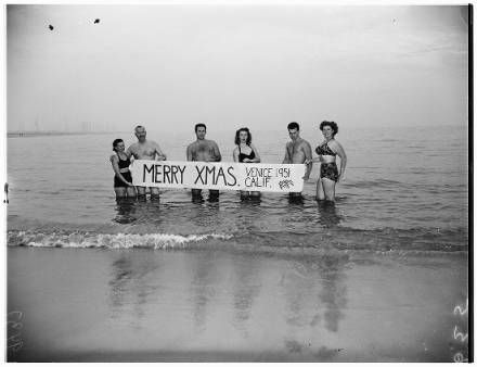 """Venice Beach enthusiasts swim in ocean with """"Merry Christmas"""" sign, 1951 :: Los Angeles Examiner Collection, 1920-1961"""