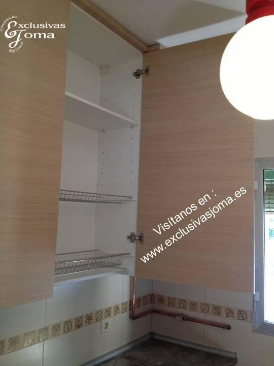 Muebles de cocina a medida con muebles altos extra grandes de 1.300mm alto cierre a techo. Muebles con acabado en color madera con ranurado efecto madera. Encimera de formica imitación a piedra natural. Visítanos en : www.exclusivasjoma.es