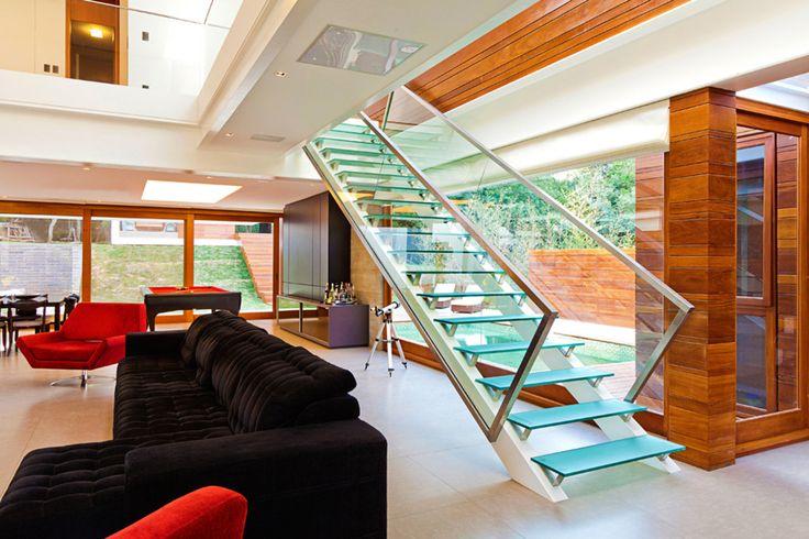 Escada moderna com corrimão de metal e balaustre de vidro. O piso ganhou um vidro verde.  https://www.homify.com.br/livros_de_ideias/28005/7-escadas-de-vidro-fascinantes