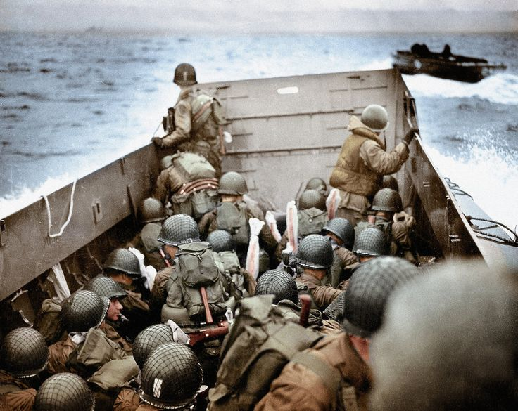 Some of the first American soldiers to attack the German defenses in Higgins Boats (LCVPs) approach Omaha Beach near Normandy, France on June 6, 1944. Plastic covers protect the soldier's weapons against from the water.
