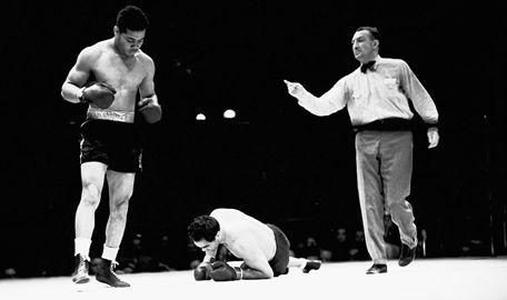 Joe Louis stands over challenger Max Schmeling as referee Arthur Donovan sends Louis to a neutral corner, June 22, 1938.