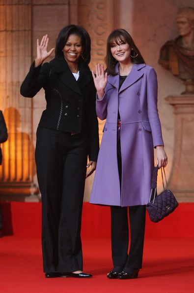 U.S. First Lady Michelle Obama (in jacket by Azzedine Alaia) and French First Lady Carla Bruni-Sarkozy wave to media upon their arrival at Rohan Palace on April 4, 2009 in Strasbourg, France