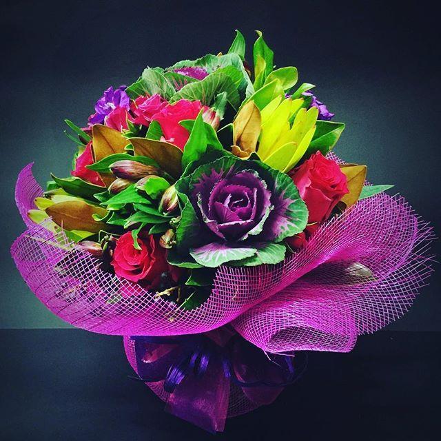 An arrangement including Kale, Roses, Leucadendron, Alstroemeria and Stock