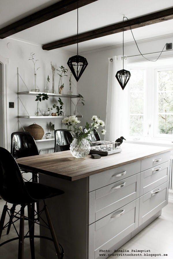 BÄNKSKIVA i mörkt trä diy, styla en hylla, hyllor, inredning, stylingtips, dekorera, dekorering, gröna blad i flaskor, grönt från skogen, hth kök, köksö, svarta barstolar, tund vas, korp, svart och vitt, vitt kök, vita väggar,