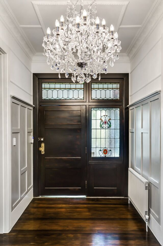 A narrower foyer featuring stained glass and an enormous crystal chandelier. While the foyer itself is small, it serves the purpose of preserving the privacy of the home when the door is opened to strangers.