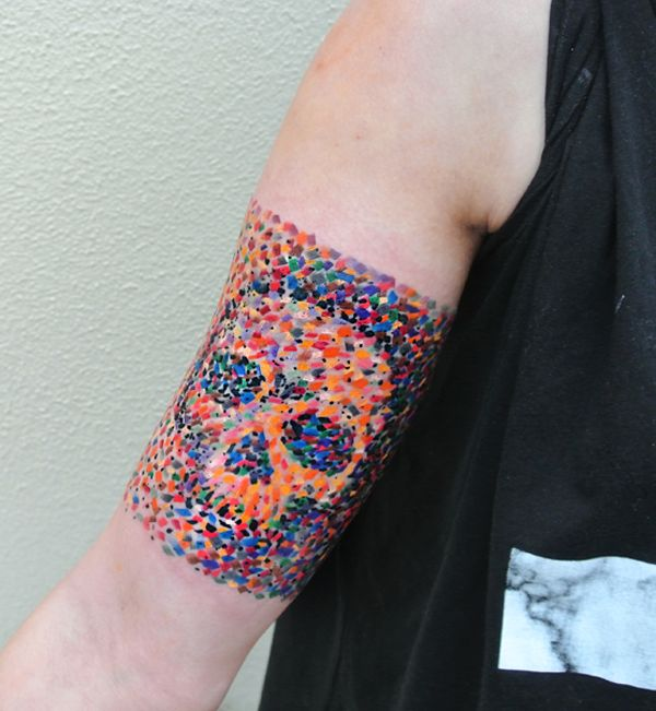 Colorful and mosaic inspired sleeve tattoo. The colorful confetti inked on the arm combines to form a skull with a sort of dark cloak draped on it. It's a wonderful contrast of the multi colored mosaic design that forms a much darker image from behind.