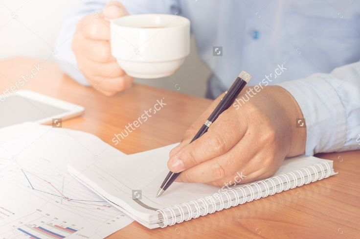 Businessman working on office desk. Writing something on notebook.Holding a coffee cup in a hand. Blurred background, Vintage concept. #business #businessman #man #professional #office #background #notebook