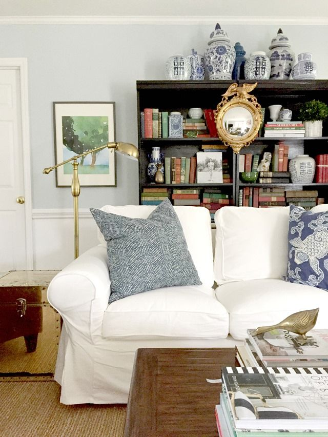 white slipcovered sofa in living room, light blue walls, blue and white, federal mirror, black bookcases